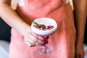 pink drink in a coupe glass with herb and flower garnish