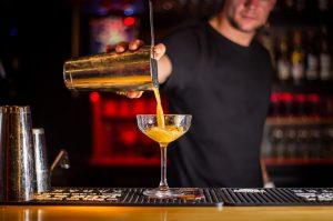 bartender using a Hawthorne strainer