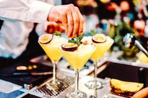 bartender putting garnish on three martinis