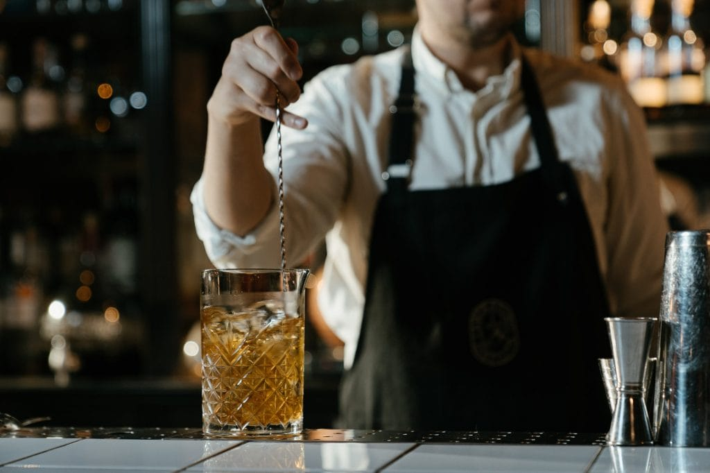 bartender stirring a cocktail in a crystal mixing glass