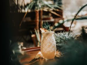 cocktail in pineapple tiki glass with pineapple garnish