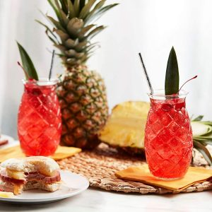 pineapple design tiki glasses with red cocktail and palm garnish