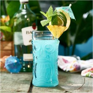 tall tiki glass with screaming face design and blue tiki drink