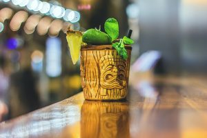 short tiki mug that looks like wood with traditional face carving with pineapple lime and mint