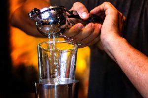 bartender squeezing lemon with a citrus press
